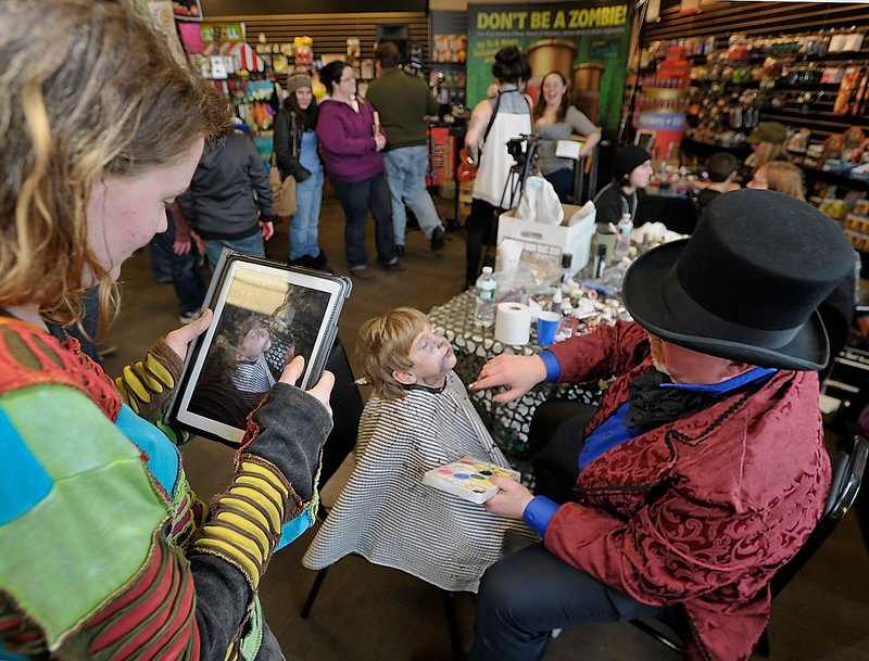 Dezzmon Clark, 5, gets a zombie makeover by Reggie Groff as his mom, Terri Wengland of Standish, takes an iPad photo.