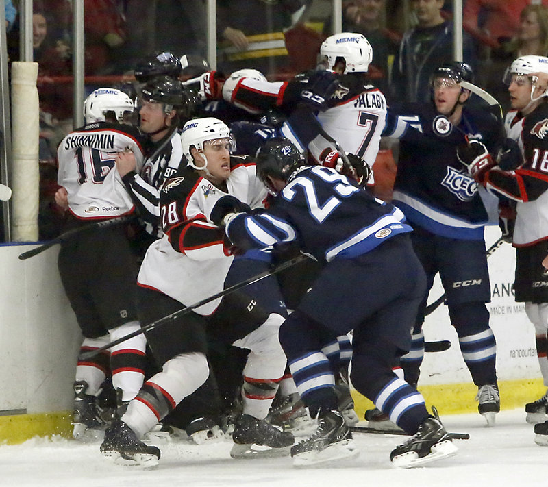 The referee earns his keep Sunday afternoon at the Androscoggin Bank Colisee in Lewiston, separating combatants during a first-period scrum between the Portland Pirates and the St. John's IceCaps.