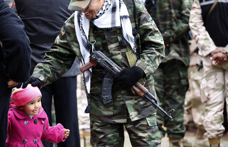 """A member of the Libyan security forces pats a child while celebrating the revolution's anniversary in Benghazi, on Sunday. In their new society, Libyans are impatient for """"transitional justice."""""""