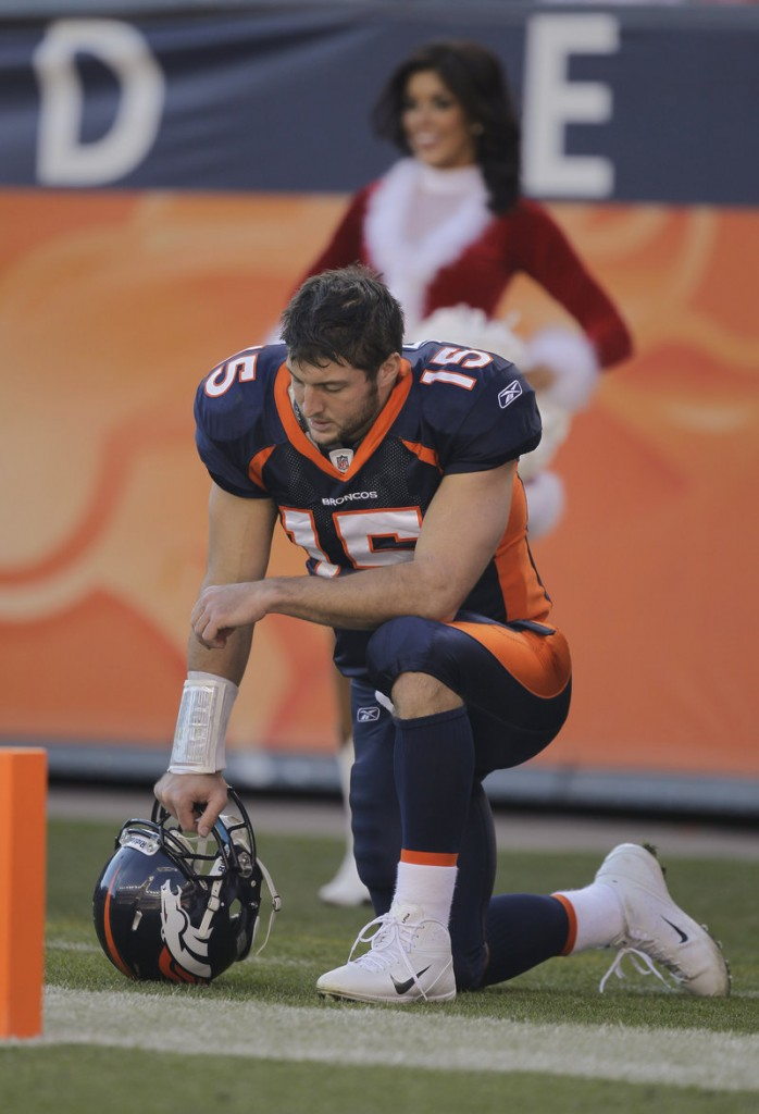 Then-Denver quarterback Tim Tebow prays on the sideline during a 2012 playoff game.