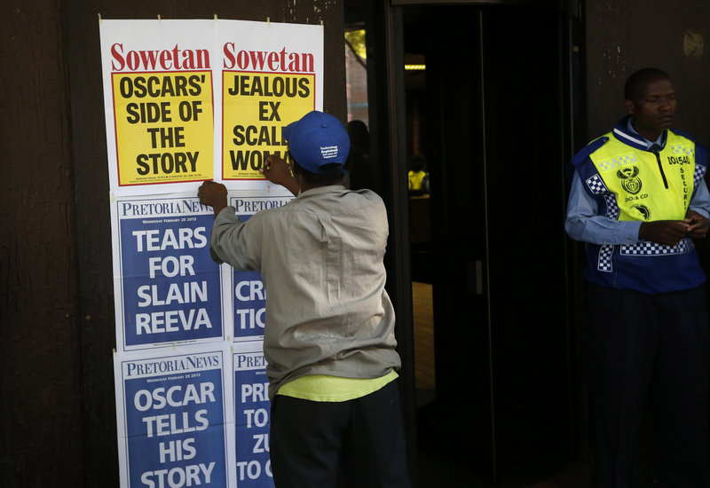 A newspaper vendor posts the headlines outside the courthouse in Pretoria, South Africa, where Oscar Pistorius has been appearing. The case is being followed closely both in South Africa and abroad.