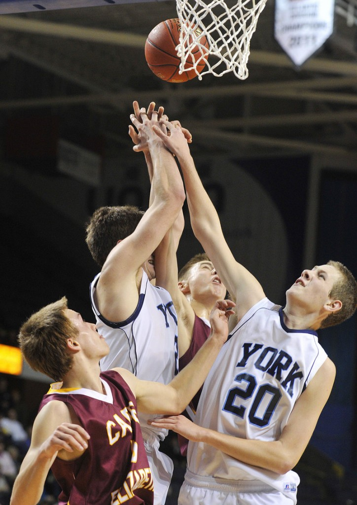 Rebound time and it's a scramble for the ball. Aaron Todd, left, and Adam Bailey of York tangle with Ethan Murphy of Cape Elizabeth.
