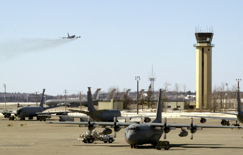 A KC-135 refueling tanker takes off at Bangor International Airport in 2003 as other refueling planes and transport planes sit below the airport control tower.