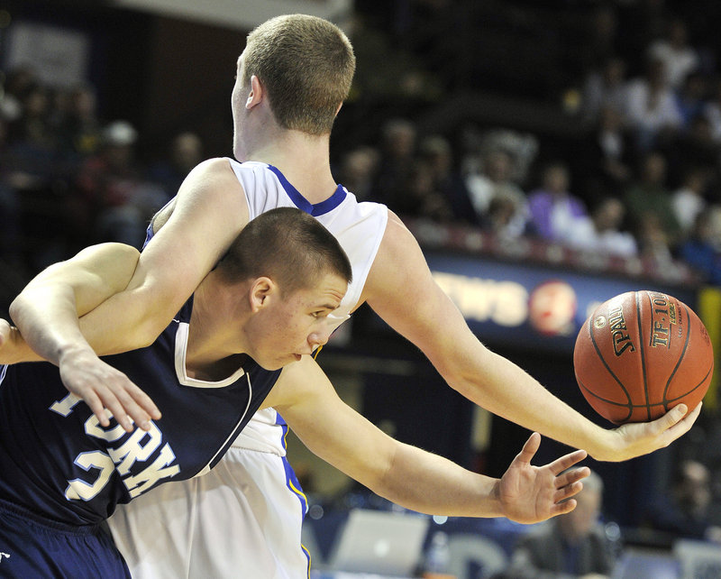 Nick Burton of Falmouth keeps the ball from Thomas Kinton of York as they get tangled during the Western Class B final in Portland.