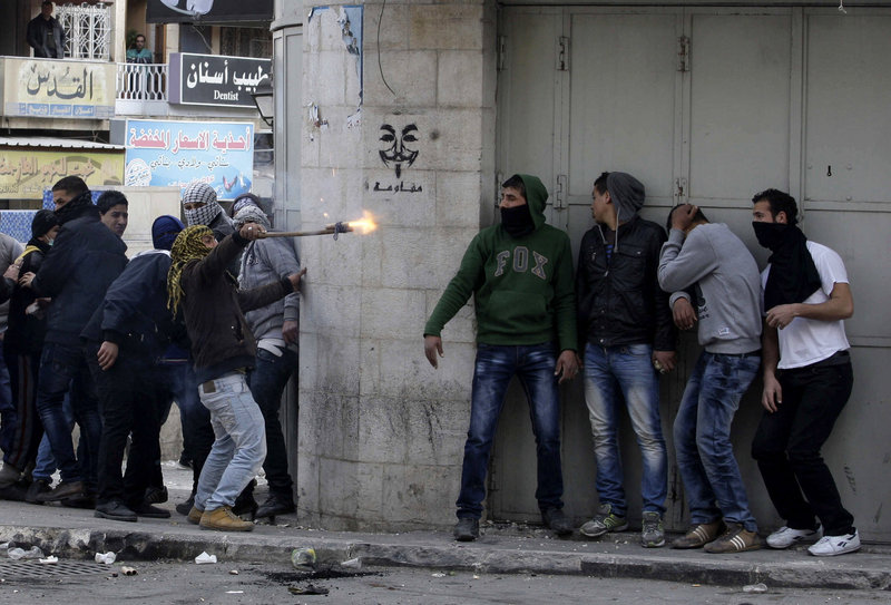Palestinians take cover during clashes with Israeli troops in the West Bank city of Hebron on Sunday, following the death of Arafat Jaradat, a Palestinian prisoner held in an Israeli prison.
