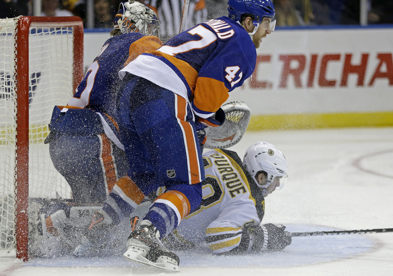 Chris Bourque of the Bruins lands beneath Islanders goalie Evgeni Nabokov and New York defenseman Andrew MacDonald in Tuesday night's game at Uniondale, N.Y. The Bruins won 4-1 – their 16th win in the last 20 games against the Islanders.