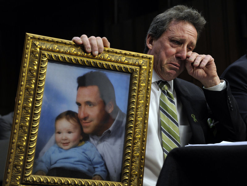 Neil Heslin, father of a Sandy Hook victim, holds a picture of himself with his late son Jesse while testifying on Capitol Hill Wednesday in favor of an assault weapons ban.