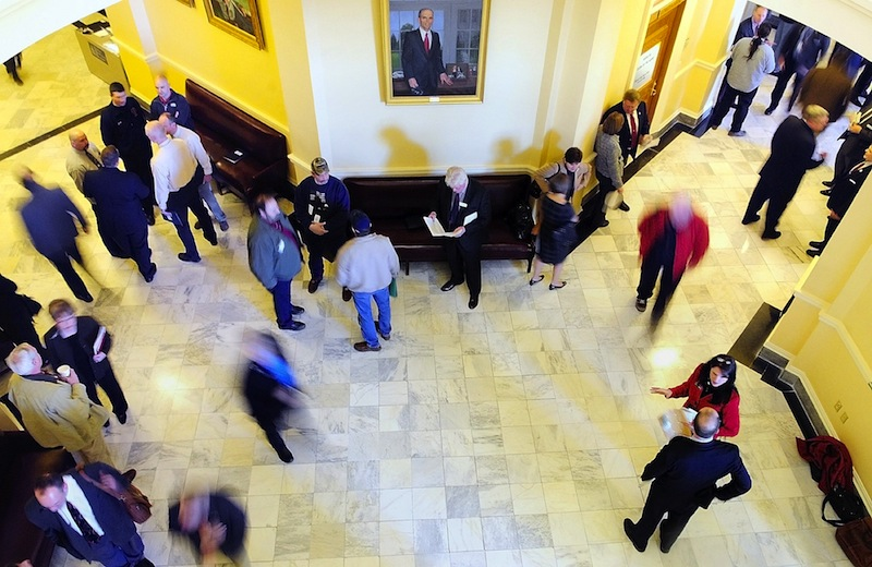 In this file photo, people move through the third floor between the House and Senate chambers at the State House in Augusta. The Maine Legislature's budget-writing committee Wednesday unanimously approved on an emergency spending plan to fix Maine's $153 million budget shortfall.
