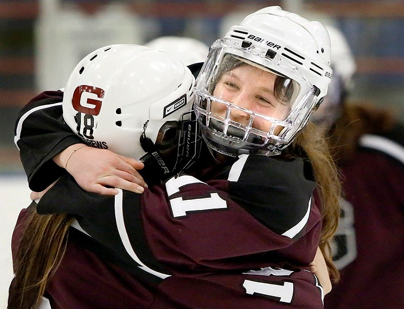 Mary Morrison, right, hugs Chesley Andrews after scoring the overtime goal Saturday night that gave Greely its second straight girls' hockey state championship with a 1-0 victory against Scarborough at Lewiston.