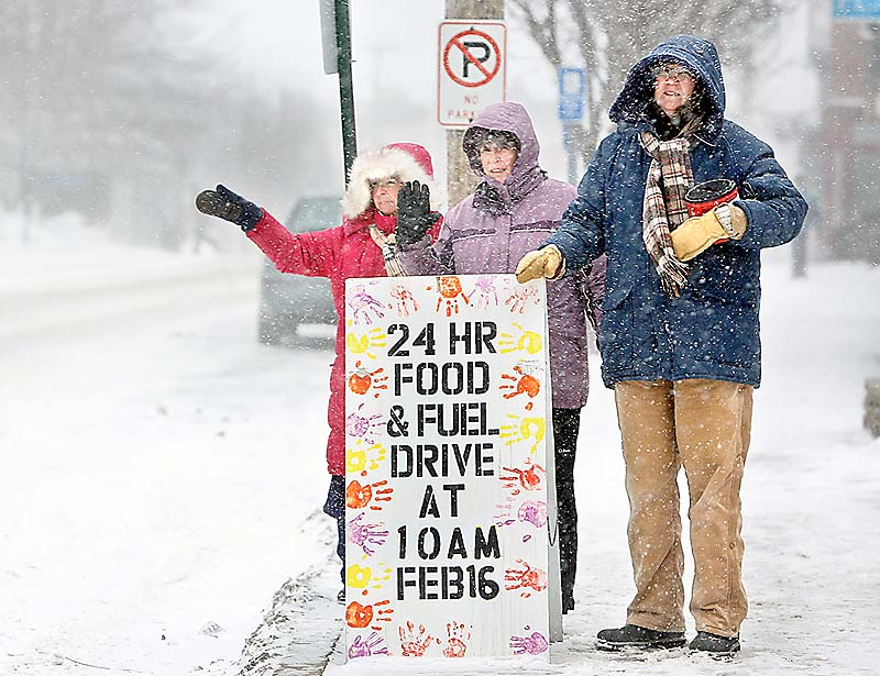 Patti Bruce, from left, Paula O'Brien and Sue Mack stand in front of the First Parish Church in Freeport and wave to passing cars Sunday during the 2013 Freeze Out, a 24-hour food and fuel drive to benefit a local food pantry and heating-assistance program.