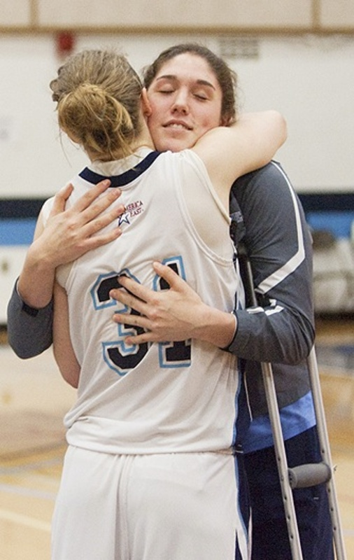 """Liz Wood, another member of the UMaine team, hugs injured Danielle Walczak after the game. """"We didn't want the season to end with (the crash),"""" said Wood, a freshman from Catlett, Va. """"I'm glad we played. I didn't think about (the crash) for the whole game."""" Walczak's injuries are unrelated to last week's accident."""
