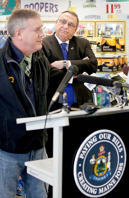 Gov. Paul LePage listens to Paul Landry, owner of Fish Bones American Grill, talk to the media about the governor's plan to pay back the hospital debt by leveraging future liquor sale revenue. The news conference took place at Roopers Beverage in Auburn on Friday.