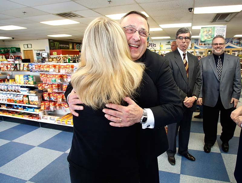 Gov. Paul LePage hugs supporter Laurie Steele after speaking to the media during his visit to Roopers Beverage in Auburn on Friday.