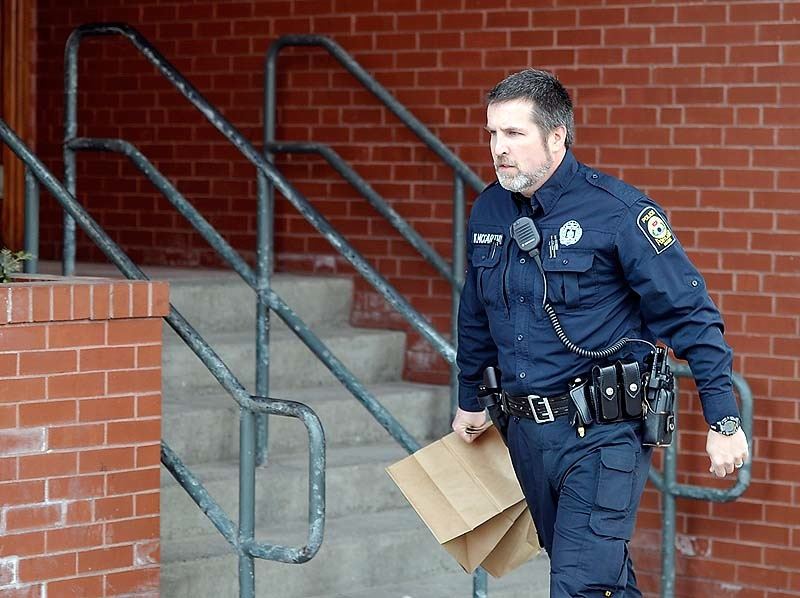 A police officer rushes out of the building with bags of evidence as police surround the Lafayette Square apartment complex in Portland after gunshots were exchanged on the 6th floor on Friday, March 15, 2013.