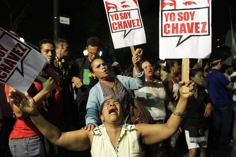 A supporter of Venezuela's President Hugo Chavez cries as she holds a sign that reads in Spanish