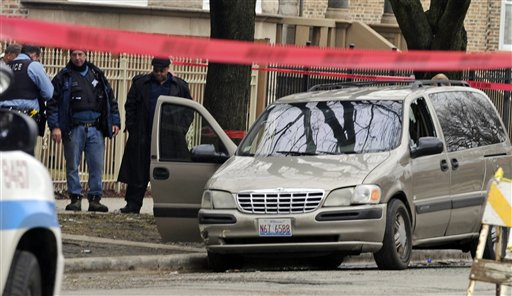 Chicago police investigate at the scene of a shooting where 6-month-old Jonylah Watkins was shot five times while her father was changing her diaper in a parked minivan in Chicago's Woodlawn neighborhood. The van can be seen with the window shattered from the shooting.