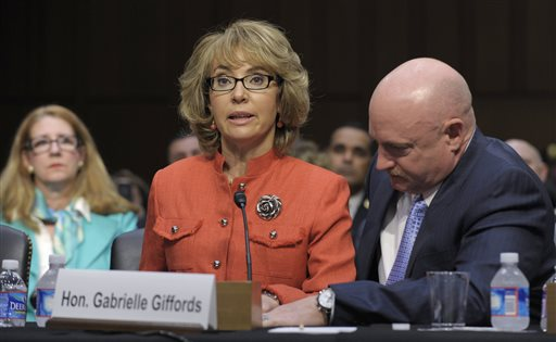 Former Arizona Rep. Gabrielle Giffords is aided by her husband, Mark Kelly, as she speaks before a Senate Judiciary Committee hearing on gun violence in this Jan. 30, 2012, photo.