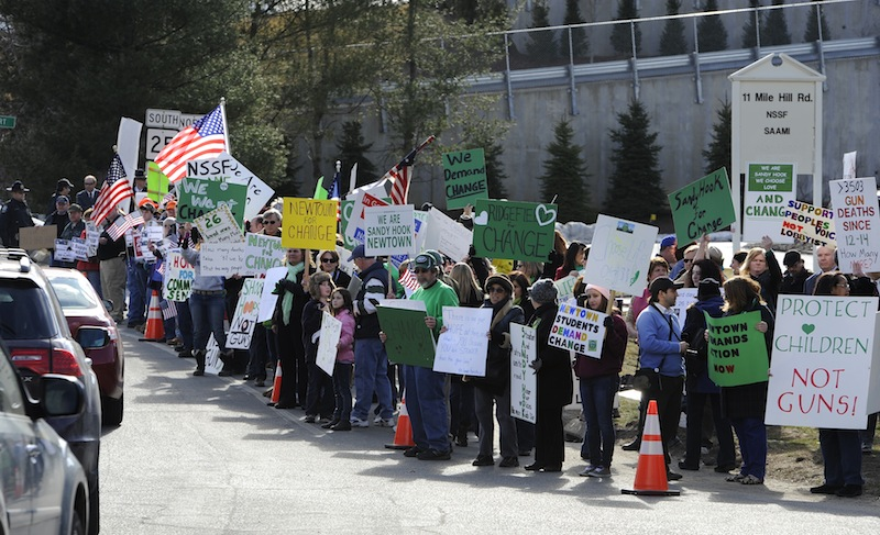 Supporters of both sides of the gun debate gather outside the National Shooting Sports Foundation headquarters in Newtown, Conn., Thursday, March 28, 2013. Search warrants released Thursday, March 28, 2013, revealed that an arsenal of weapons including guns, more than a thousand rounds of ammunition, a bayonet and several swords was seized at Adam Lanza's home. Lanza killed his mother, Nancy Lanza in their home before he forced his way into Sandy Hook Elementary School in Newtown, Conn, killing 26 people. (AP Photo/Jessica Hill)