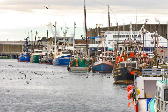 Federal fishery managers told beleaguered New England fishermen on Friday, March 1, 2013 that they'll try to cover the millions it costs to hire required at-sea catch monitors. Above, commercial fishing boats in Gloucester, Mass.