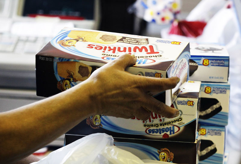 In this Nov. 16, 2012 file photo, a cashier rings up boxes of Hostess Twinkies and Cup Cakes at the Hostess Brands' bakery in Denver.