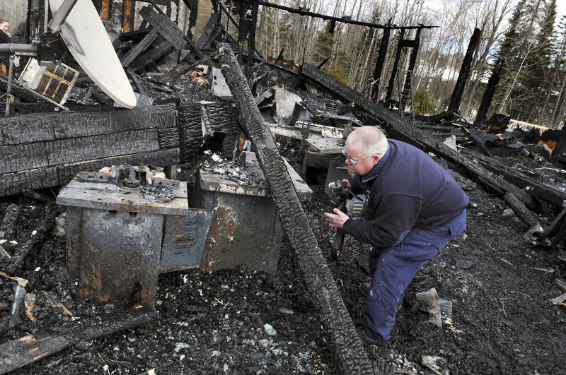 Investigator Ken MacMaster of the State Fire Marshal's Office examines machines in the cabinet shop of the Whitehouse residence in Mount Vernon Sunday. The building burned early Sunday morning.