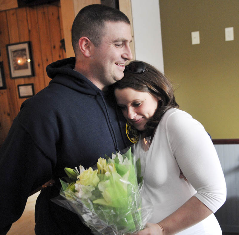 Megan McGuire hugs her husband, Travis, Wednesday March 20, 2013 moments after he surprised her by returning early from an Army deployment in Afghanistan to be present for the birth of their first child. Travis McGuire walked into the Depot in Gardiner and gave his wife a bouquet of flowers as she dined with family and friends.