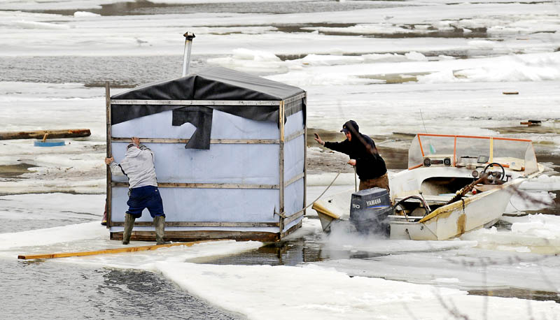 Jimmy Worthing, left, and a member of his smelt camp crew retrieve a shack floating on a sheet of ice Tuesday in the Kennebec River in Randolph after several shacks drifted away from Worthing's Smelt Camps. Worthing and a crew broke ice with a boat and towed several stray shacks back to shore.