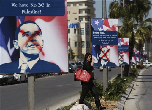 A Palestinian woman walks past vandalized posters showing President Barack Obama in the West Bank city of Ramallah on Thursday.