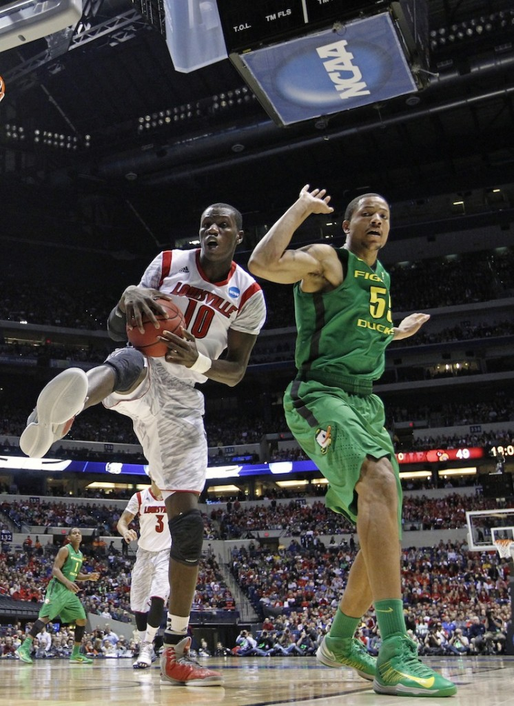 Louisville center Gorgui Dieng (10) grabs a rebound against Oregon center Tony Woods (55) during the second half of a regional semifinal in the NCAA college basketball tournament, Friday, March 29, 2013, in Indianapolis. (AP Photo/Michael Conroy)