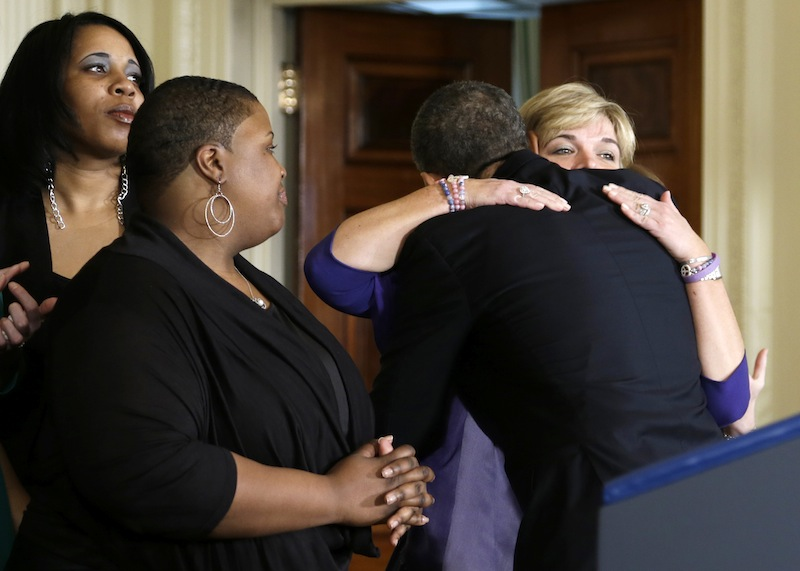 President Barack Obama hugs a woman in the East Room of the White House in Washington, Thursday, March 28, 2013, after he spoke about gun violence. The president was joined by what the White House said was mothers, law enforcement officials, victims of gun violence, who the White House did not want to name. (AP Photo/Carolyn Kaster)