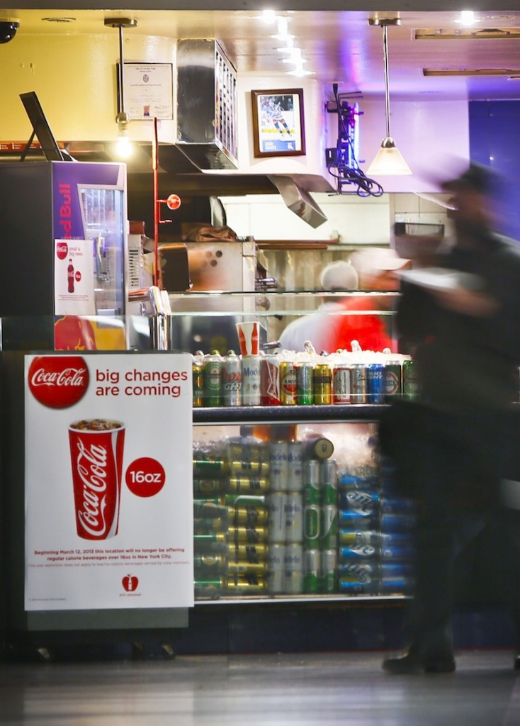 In this March 8, 2013 file photo, a Coca-Cola poster about the city's anticipated beverage ban is displayed at a pizza shop at New York's Penn Station. New York City's groundbreaking limit on the size of sugar-laden drinks has been struck down by a judge shortly before it was set to take effect. The restriction was supposed to start Tuesday, March 12, 2013. The rule prohibits selling non-diet soda and some other sugary beverages in containers bigger than 16 ounces. It applies at places ranging from pizzerias to sports stadiums, though not at supermarkets or convenience stores. (AP Photo/Bebeto Matthews)