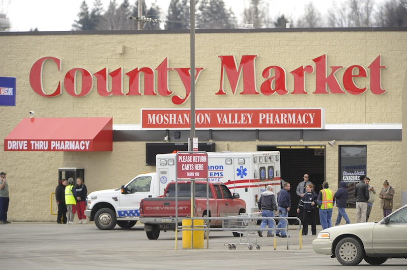 State police work the scene of a shooting Thursday, March 28, 2013, at the County Market grocery store on the outskirts of Philipsburg, Pa. Pennsylvania State Police say the gunman in a supermarket shooting is a retired state trooper, and the woman he shot before killing himself had been his wife. State police spokeswoman Maria Finn said Thursday troopers were working to notify their closest victims, holding up public identification of the two. (AP Photo/Centre Daily Times, Nabil K Mark)
