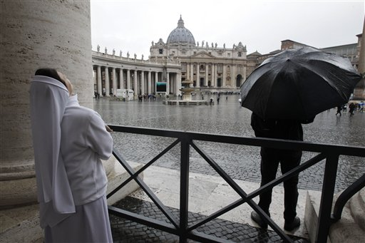 A nun watches the rain in St. Peter's Square during the second day of the conclave to elect a new pope at the Vatican on Wednesday.