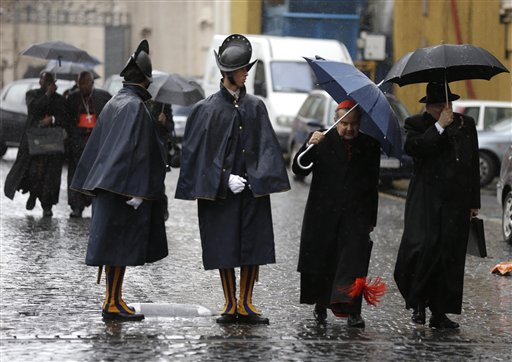Cardinal Carlo Caffarra, second from right, and Cardinal Raymond Leo Burke, right, walk past two Swiss guards as they leave after a meeting at the Vatican on Friday.