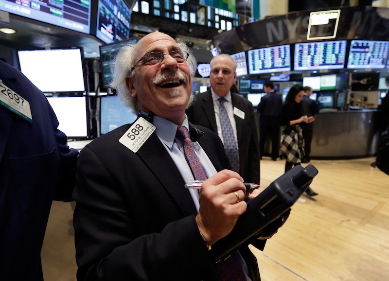 Trader Peter Tuchman smiles as he works on the floor of the New York Stock Exchange on Tuesday. The Dow reached a new high Tuesday.
