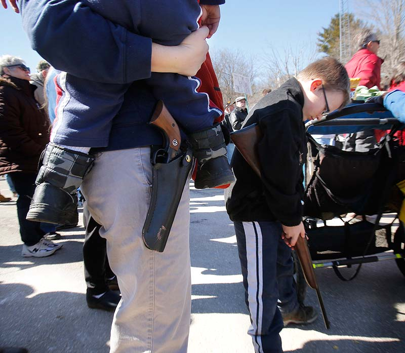 Suzanne Hiltz of Chelsea holds her son, Samson, 2, with a Ruger Single-Six .22 caliber revolver on her hip, while attending a rally in Wiscasset on Saturday protesting gun control legislation and supporting gun rights. At right is Hiltz's son Jonah, 7, holding a .22 caliber youth model rifle.