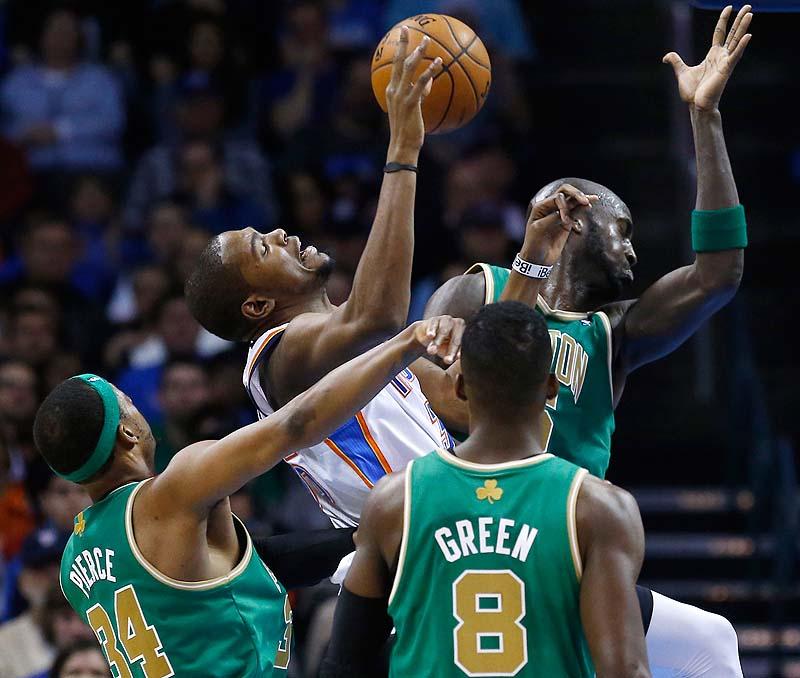 Oklahoma City Thunder forward Kevin Durant, with ball, is fouled by Boston Celtics forward Paul Pierce, 34, as he shoots among Pierce, forward Kevin Garnett, 5, and forward Jeff Green, 8, in Sunday's game at Oklahoma City. The Thunder won, 91-79.