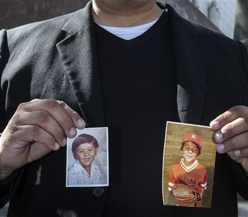 Michael Duran, a plaintiff in a sex abuse settlement with the Roman Catholic Archdiocese of Los Angeles, holds up pictures of himself when he was a child during a news conference to announce details of a nearly $10 million settlement of their lawsuits against the Archdiocese of Los Angeles Thursday, March 14, 2013. Duran was molested by ex-priest Michael Baker, who is now in jail after pleading guilty pleaded to a dozen sex charges. The U.S. church's challenges include recovering from the clergy sexual abuse scandal, which has resulted in the bankruptcies of prominent archdioceses and cost the Church in America an estimated $3 billion in legal settlements. (AP Photo/Damian Dovarganes)