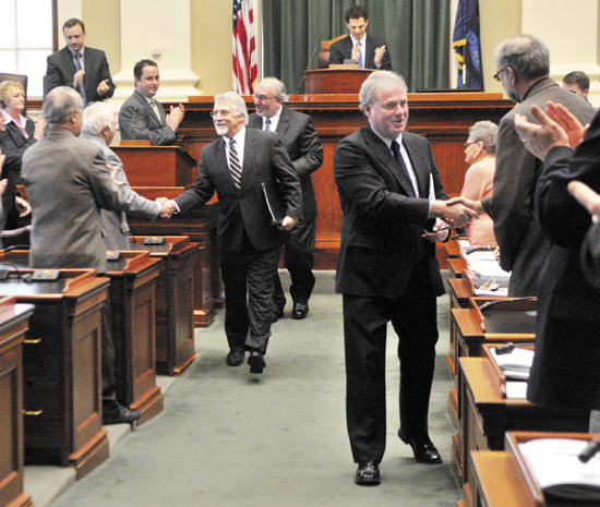 William Brennan, president of Maine Maritime Academy, left, John Fitzsimmons, president of the Maine Community College System, and James Page, chancellor of the University of Maine System, shake hands as they leave the House chamber after giving their State of Education addresses on Thursday at the State House in Augusta.