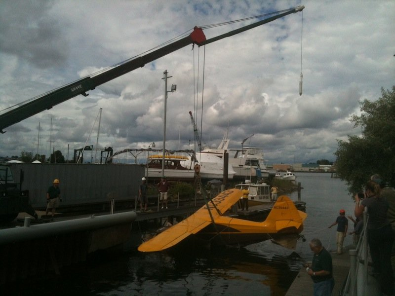 The Stinson plane involved in the fatal crash at Fort Williams Park is lifted onto the dock at South Port Marine in South Portland in this June 26, 2012, photo.