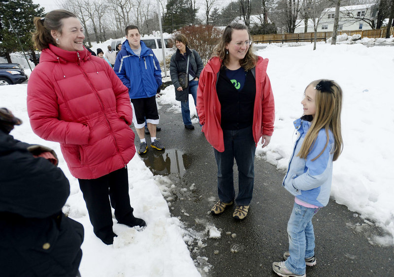 """Cheryl Denis, center, greets her daughter Ella, 9, at Lyseth Elementary School on Thursday. """"I think it's great. It's really important for kids, not only for the health reasons, but it's just a great way to start the day,"""" Denis said of the planned walking program. At left is Kelly Frost."""