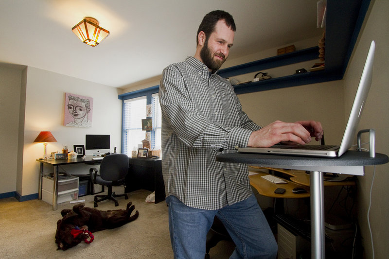 """Mike MacDonald, a software engineer, works at home in Cape Elizabeth on Friday. A telecommuter since 2005 for a company based in California, MacDonald acknowledges, """"sometimes there's no substitute for hashing things out together on a whiteboard and solving a problem."""""""