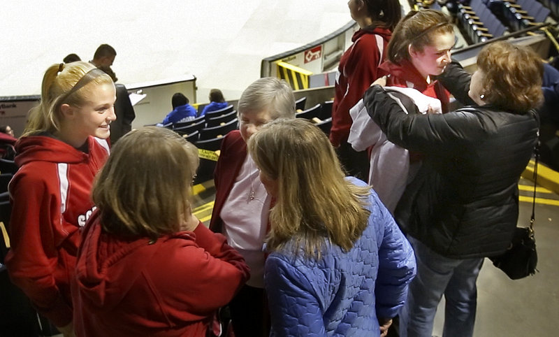 Senior Courtney Alofs is comforted by her mother, Carlene, far right, after the Scarborough High School girls basketball team played its final game Feb. 22. At left, senior Maria Philbrick talks with her family members.
