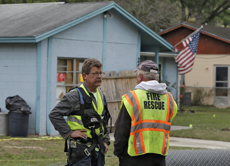 Engineers discuss their findings while investigating a sinkhole that opened up beneath a home in Seffner, Fla., on Thursday.