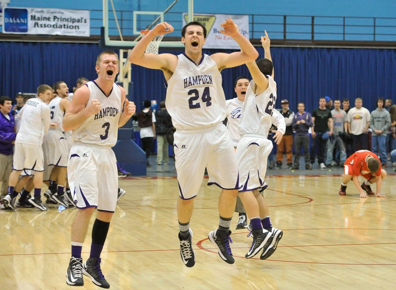 Tyler Norris, 24, starts the celebration for Hampden Academy with Brian Fickett, left, after the 45-41 victory against South Portland at Augusta.
