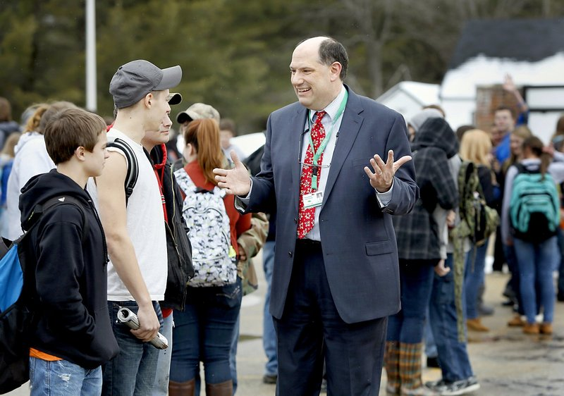 """Massabesic High School Principal Christian Elkington visits with students waiting for a bus at the end of the school day in Waterboro on Friday. """"We're being told, even if we're making gains, they're not good enough,"""" Elkington said."""