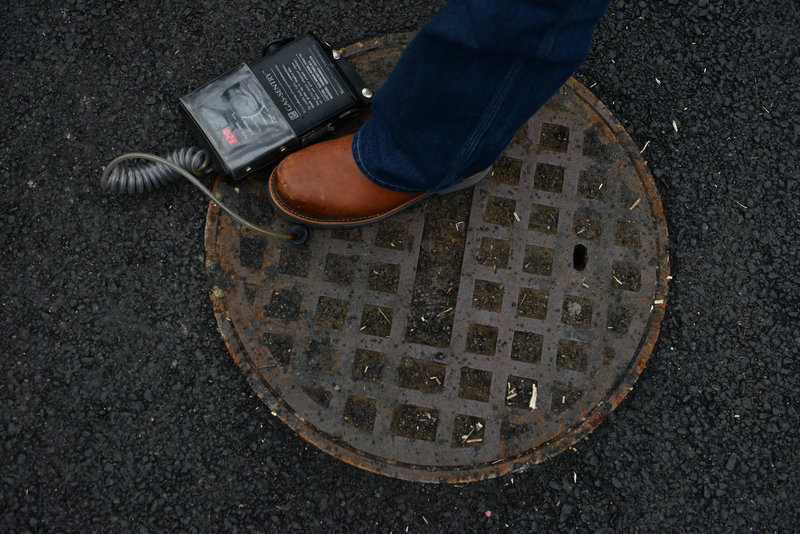Bob Ackley, a gas leakage specialist, uses a combustible gas indicator to test the outpouring of methane gas from a manhole in the affluent Spring Valley neighborhood of Washington, D.C.