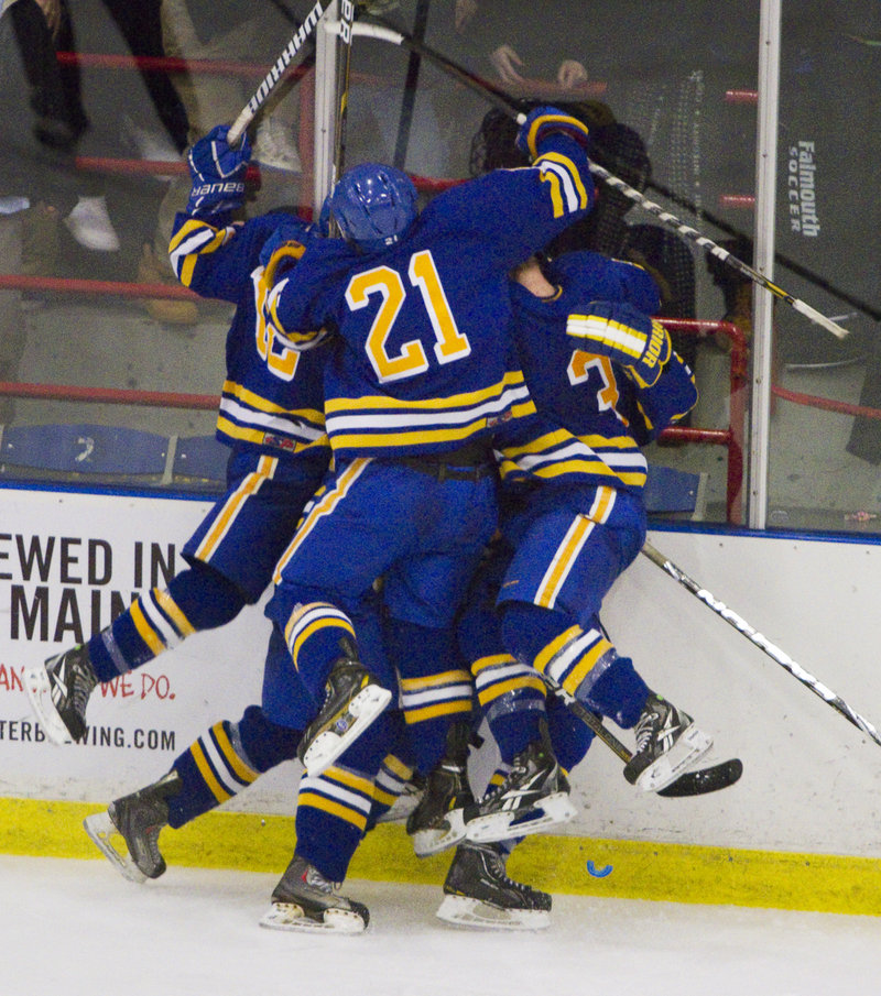 Isac Nordstrom of Falmouth is mobbed by teammates Tuesday night after scoring the tying goal with 3:26 remaining. The Yachtsmen added a goal moments later to beat Scarborough and win Western Class A.