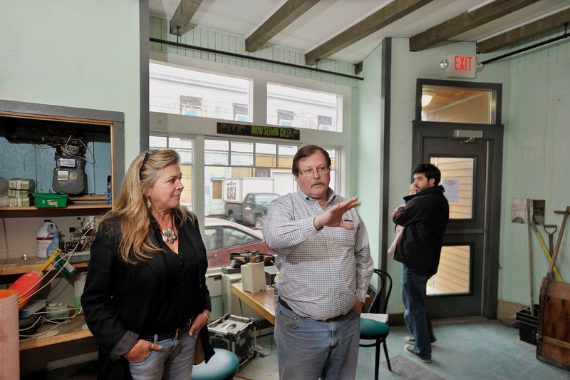 With general manager Beth Poitras, left, new Porthole Restaurant & Pub owner Ken Macgowan talks about the planned April 1 opening. Macgowan's son Garrett, right, stopped by with daughter Aria, 11 months, to check out the improvements.