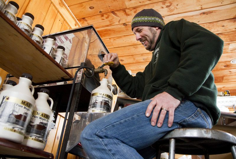 """Keith Harris of Harris Farm on Buzzell Road in Dayton fills jugs of maple syrup at the farm's sugarhouse last Thursday. """"What I want is what normal used to be,"""" he said, speaking of this month's weather."""